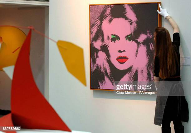 Christies press officer Hannah Schmidt stands with 'Brigitte Bardot' by Andy Warhol dated 1974 which is estimated to sell for between 1000 and 2...