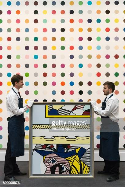 Christies staff hold a painting titled Two Paintings With Dado by artist Roy Lichtenstein with a sale estimate of £2000£3000 The background painting...
