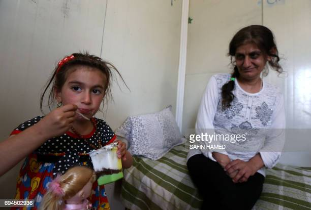 Christina a sixyearold Iraqi Christian girl eats a dessert as she meets with her mother in Ashti 2 camp for displaced Christians in Arbil the capital...