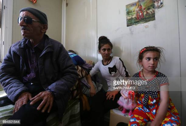 Christina a sixyearold Iraqi Christian girl holds a doll as she sits next to her father during a meeting with her family in Ashti 2 camp for...
