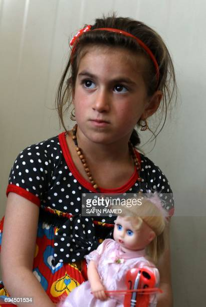 Christina a sixyearold Iraqi Christian girl holds a doll during a meeting with her family in Ashti 2 camp for displaced Christians in Arbil the...
