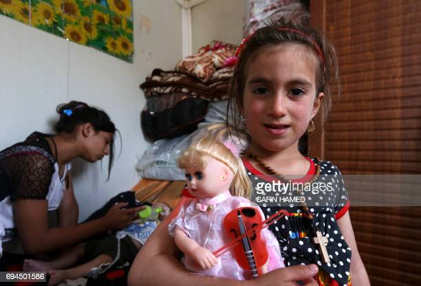 TOPSHOT Christina a sixyearold Iraqi Christian girl holds a doll during a meeting with her family in Ashti 2 camp for displaced Christians in Arbil...