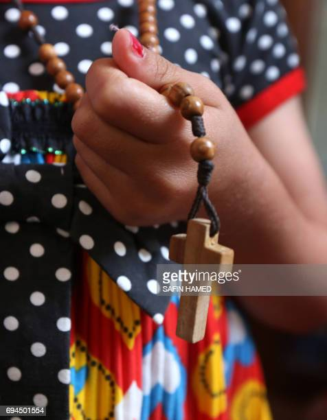 Christina a sixyearold Iraqi Christian girl holds a rosary with a crucifix hanging at its end as she meets with her family in Ashti 2 camp for...