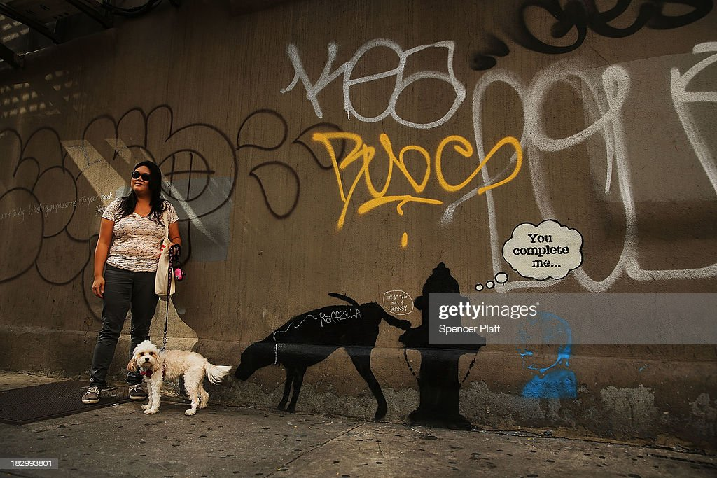 Christina Ng poses in front of a new Bansky work with her dog Cece on October 3, 2013 in New York City. New work by the mysterious British street artist Banksy has appeared in New York after announcing a a month-long residency in the city. Three works in total have appeared in recent days with two of them quickly being vandalized by other graffiti.