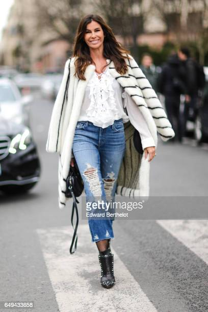 Christina Pitanguy wears a striped white fur coat a white lace shirt blue ripped jeans outside the Moncler Gamme Rouge show during Paris Fashion Week...