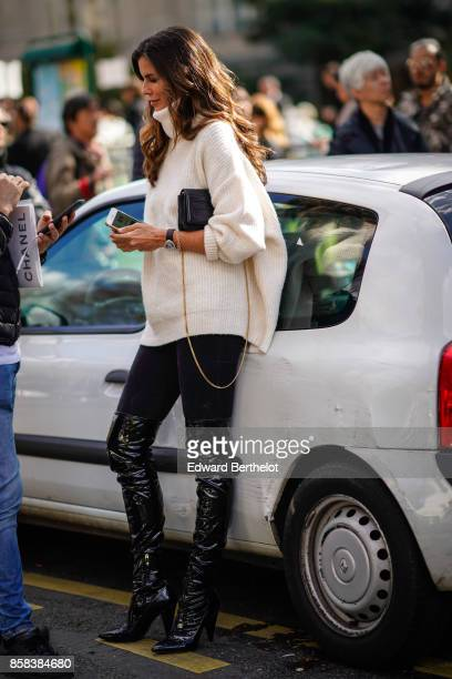 Christina Pitanguy wears a white pull over black pants black thigh high leather boots outside Moncler during Paris Fashion Week Womenswear...