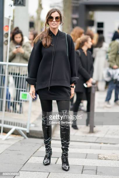 Christina Pitanguy wears sunglasses a black hoodie black pants black boots and attends Le Defile L'Oreal Paris as part of Paris Fashion Week...