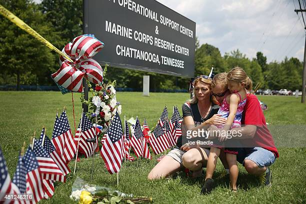 Christina Reed Aaron Workman and Julia Morrison pay their respects at a memorial setup at the entrance to the Navy Operational Support Center and...