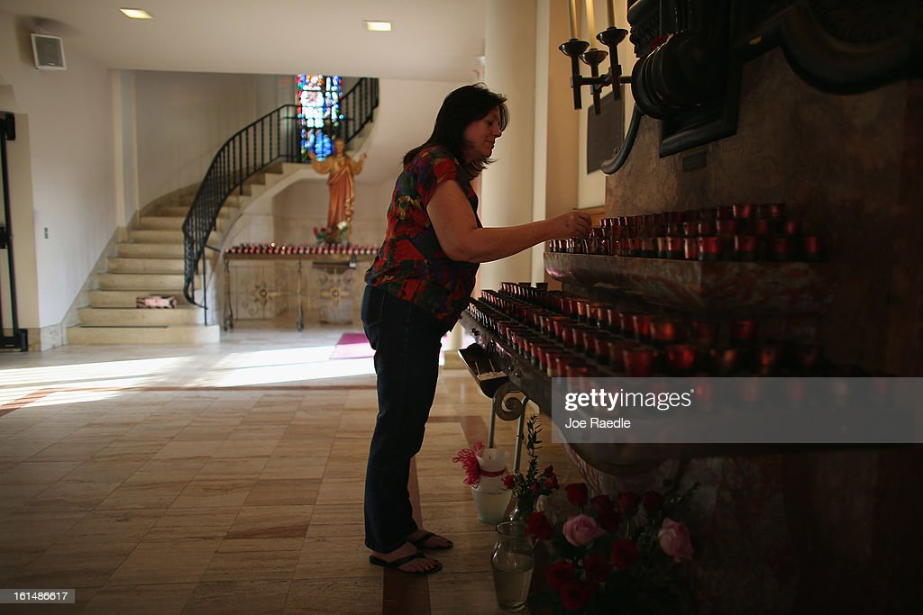 Christina Smith lights candles before a mass at the Church of the Little Flower on February 11, 2013 in Coral Gables, Florida. Parishioners today were dealing with the unexpected news that Pope Benedict XVI announced his retirement, now the wait begins to learn who his successor will be.