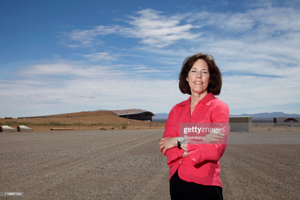 Christine Andersen, executive director of Spaceport America, stands for a portrait outside the Terminal Hangar Facility, background left, at the spaceport in Sierra County, New Mexico, U.S., on Thursday, July 14, 2011. The future home of Virgin Galactic is behind schedule and Andersen says it won't generate as many jobs as backers once claimed. Photographer: Christ Chavez/Bloomberg via Getty Images Christine Andersen