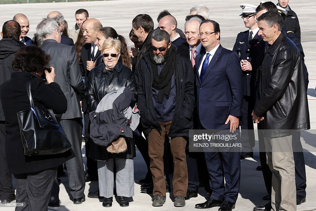 Christine Cauhape, the sister (L) of Former French hostage Marc Feret takes a picture of his brother (C) posing with his mother Francoise Feret (C-L) and French President Francois Hollande (R) upon his arrival at the military airport of Villacoublay outside Paris, on October 30, 2013. Four French hostages who were kidnapped by Al-Qaeda in the Islamic Maghreb in northern Niger in 2010 have been released on October 29. Frenchmen Thierry Dol, Daniel Larribe, Pierre Legrand and Marc Feret were working for French nuclear giant Areva when they were kidnapped on September 16, 2010, from a uranium compound in Arlit, north-central Niger. AFP PHOTO / KENZO TRIBOUILLARD
