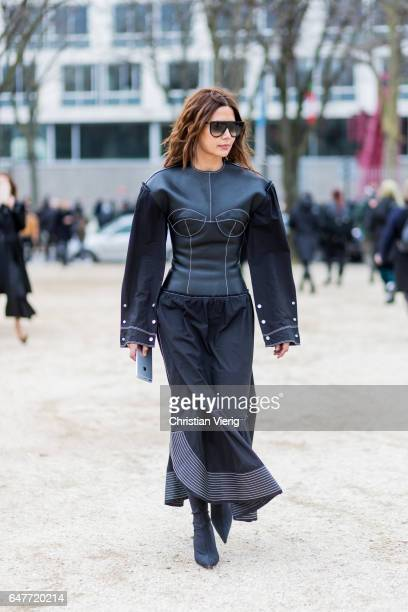 Christine Centenera wearing a black leather dress outside Loewe on March 3 2017 in Paris France