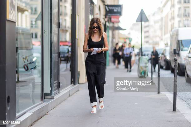 Christine Centenera wearing black pants with white hem white heels black top outside Valentino during Paris Fashion Week Haute Couture Fall/Winter...