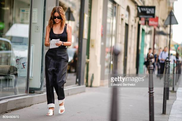 Christine Centenera wears sunglasses a black lowneck tank top black pants white shoes outside the Valentino show during Paris Fashion Week Haute...