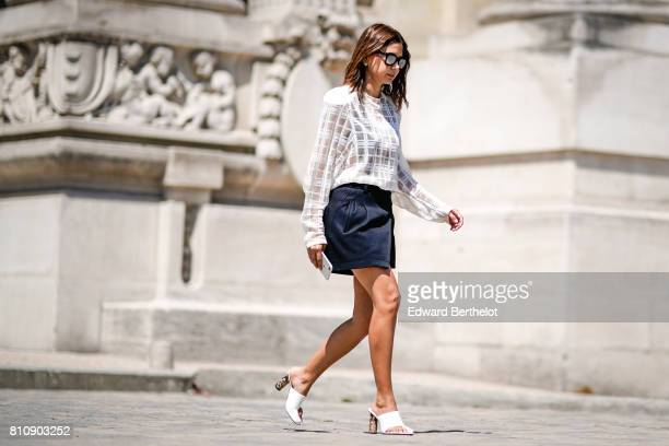 Christine Centenera wears sunglasses a white lace mesh top a black skirt white shoes outside the Chanel show during Paris Fashion Week Haute Couture...