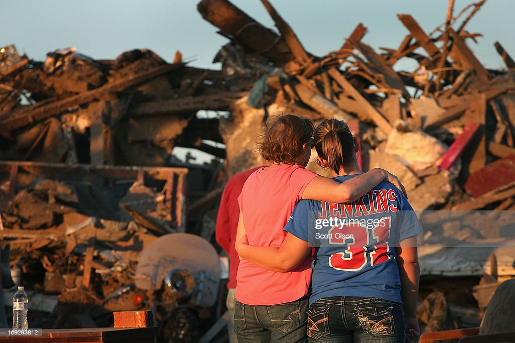 Christine Jones (L) is comforted by her daughter Ashley as they stand in front of Christine's home which was destroyed when a tornado ripped through the area on May 22, 2013 in Moore, Oklahoma. The tornado of at least EF4 strength and two miles wide touched down May 20 killing at least 24 people and leaving behind extensive damage to homes and businesses. U.S. President Barack Obama promised federal aid to supplement state and local recovery efforts.