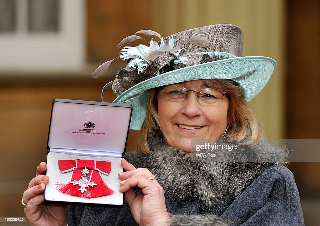 Christine Kerr proudly holds her his Member of the British Empire (MBE) medal after it was presented to her by the Prince of Wales during the Investiture ceremony at Buckingham Palace on January 25, 2013 in London, England.