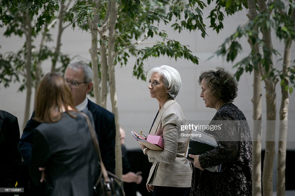 Christine Lagarde, managing director of the International Monetary Fund (IMF), center, walks through an atrium during the IMF and World Bank Group Spring Meetings in Washington, D.C., U.S., on Saturday, April 20, 2013. The IMF's Managing Director said the euro area has the only central bank with enough leeway to take more measures to boost growth as low interest rates fail to trickle down to the region's economy. Photographer: Andrew Harrer/Bloomberg via Getty Images