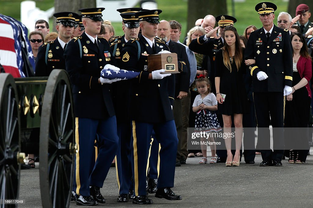 Christine Phillips, the widow of Staff Sergeant Francis G. Phillips, stands with her Four-year-old daughter, Sophia Phillips, as a U.S. Army burial team carries an urn with Phillips' remains during a burial service at Arlington National Cemetery May 20, 2013 in Arlington Virginia. Phillips, from Meridian, New York was killed in combat in the Maiwand district of Afghanistan when the vehicle he was riding in was struck by an improvised explosive device.