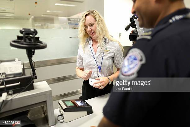 Christine Rolin prepares to pass her iphone over a scanner as she uses the new mobile app for expedited passport and customer screening being...