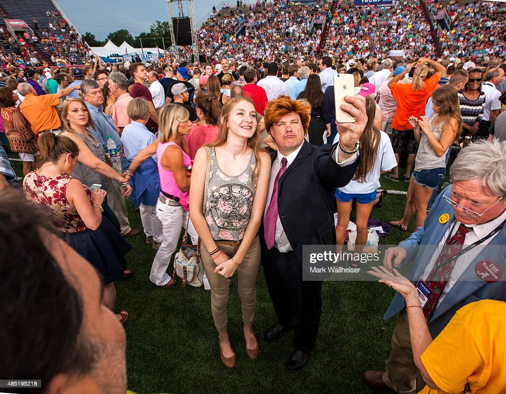 Christinia Matis, of Coden, Alabama, poses with Mobile radio DJ Matt McCoy dressed up as Donald Trump prior to the arrival of U.S. Republican presidential candidate Donald Trump at Ladd-Peebles Stadium on August 21, 2015 in Mobile, Alabama. The Donald Trump campaign moved tonight's rally to a larger stadium to accommodate demand.