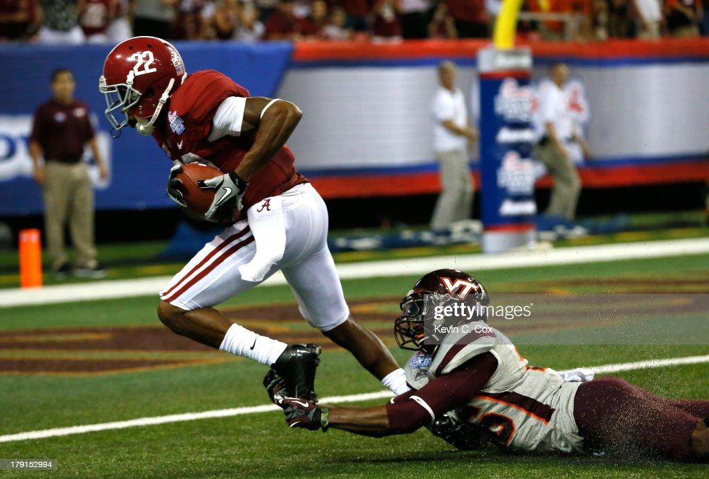 Christion Jones #22 of the Alabama Crimson Tide scores a touchdown against Desmond Frye #26 of the Virginia Tech Hokies at Georgia Dome on August 31, 2013 in Atlanta, Georgia.