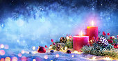 Red Candles With Christmas Ornament And Light On Snow