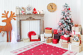 Christmas and New Year details of home interior - wooden deer, mantelpiece with candles, Eve tree and presents.