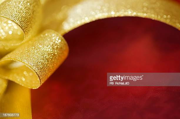 Christmas background of gold gift ribbon and bow on red