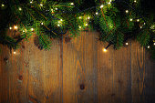 fir twigs with christmas lights on wooden background