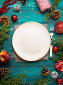 Christmas dark green background with empty dish and cutlery. Festive holiday dinner concept