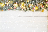 Christmas background with fir tree and decoration on white wooden board.