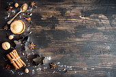 Christmas spices and baking ingredients on wooden background. Cinnamon, anise stars, nutmeg, cardamom, cloves, brown sugar and cocoa powder for Christmas cake, cookies.