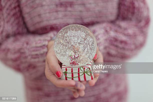 Christmas ball with reindeer and snow in a hand