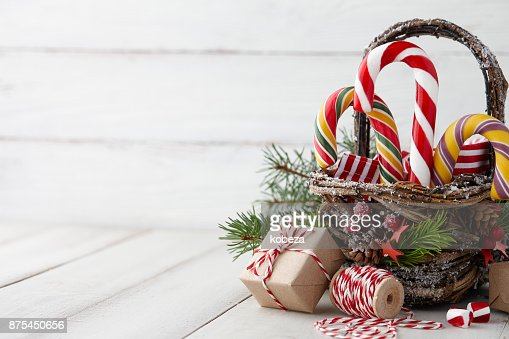 Christmas basket with candy canes on white planks : Stock Photo