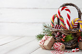 Christmas wicker basket with striped candy canes and gifts on white wooden table, festive decoration