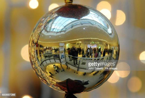 A Christmas bauble reflects the scene at Lakeside shopping centre in Essex where shoppers were out in force with less than two weeks before the...