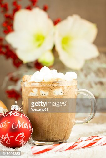 Christmas bauble, sugar cane and glass of hot chocolate with cream and marshmallows on artifical snow