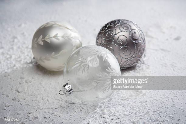 Christmas baubles laying on snowy underground.