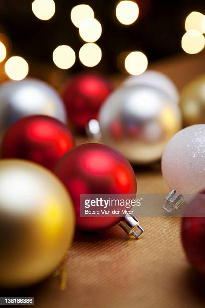 Christmas baubles on table with tree in background