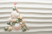 Christmas beach background with a creative arrangement of seashells forming a Xmas tree on the textured sand with ribbed lines