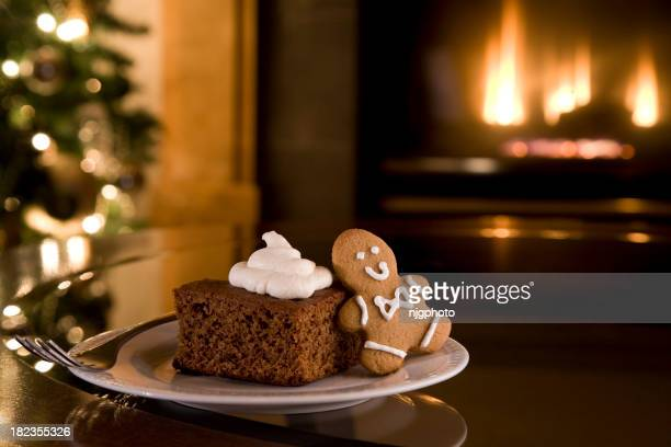 Christmas cake and cookie on a table in front of fireplace