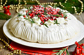 Christmas cake 'Pavlova' with cranberry decorated with rosemary leaves.