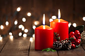 Two red Christmas candles with Christmas decoration on rustic wood table. Christmas lights are at the background. The candles are at the right side of an horizontal frame. Predominant colors are brown