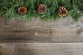 Christmas card on wooden background with snow fir tree and pine cones. View with copy space