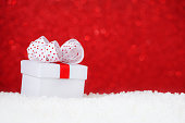 christmas card with a present in snow, red background, bokeh
