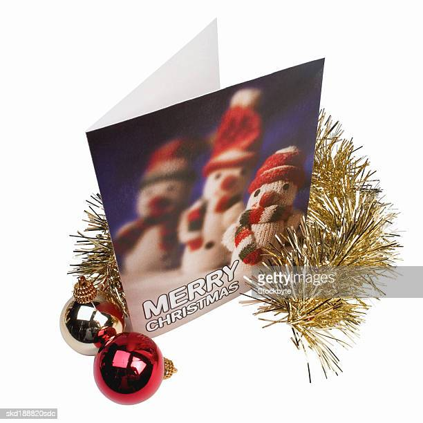 Christmas card with snowmen on it with tinsel and baubles