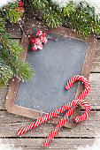 Christmas candy cane and snow fir tree on wooden table. Top view with chalkboard for your greetings