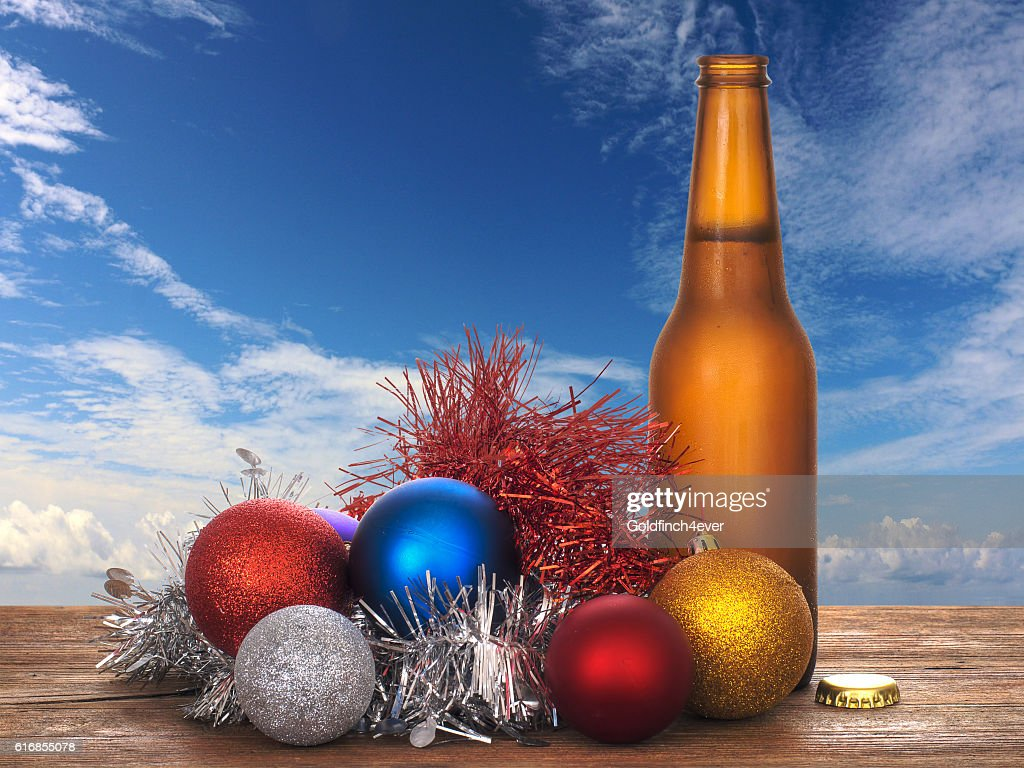 Christmas cheer - cold beer and baubles, sunshine sky. : Stock Photo