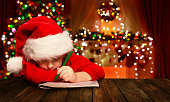 Christmas Child Write Letter to Santa Claus, Kid in Santa Hat Writing Wish List, unfocused lights background